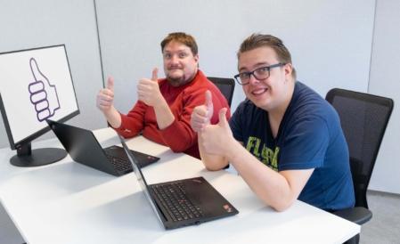 Kaksi ihmistä istuvat tietokoneen äärellä peukalot ylhäällä.