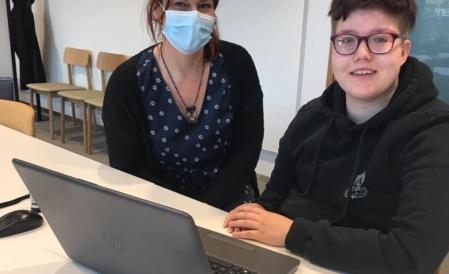 Tietokoneen äärellä kaksi ihmistä. Toinen ryhmän vetäjä, toinen opiskelija.