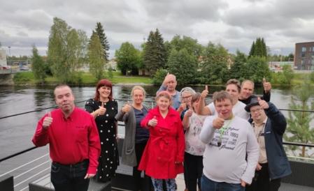 Ryhmäkuva, jossa 11 ihmistä seisoo terassilla toisen käden peukalo pystyssä.