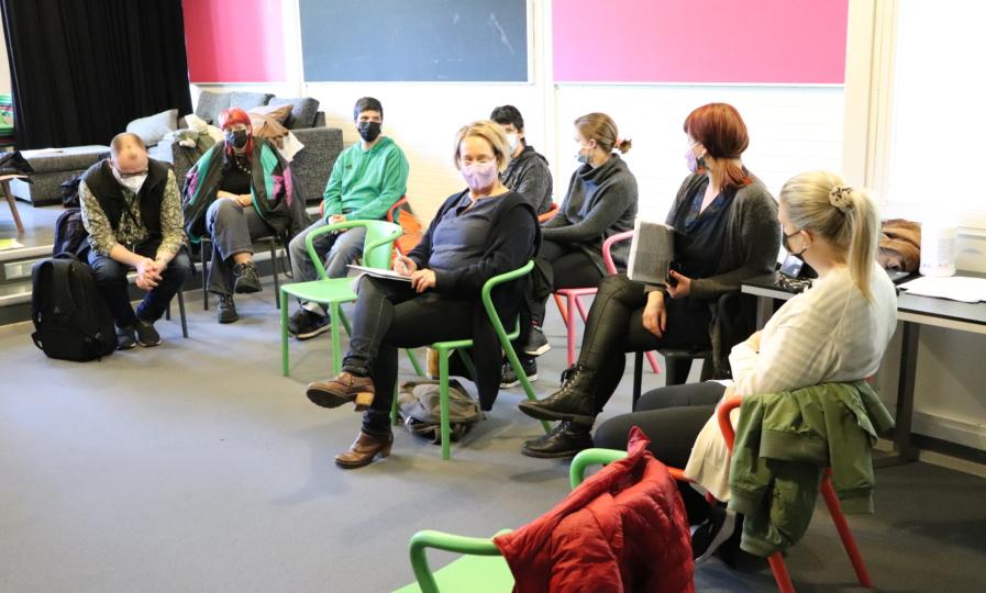 Ryhmä ihmisiä istuu tuoleilla ja keskustelee.