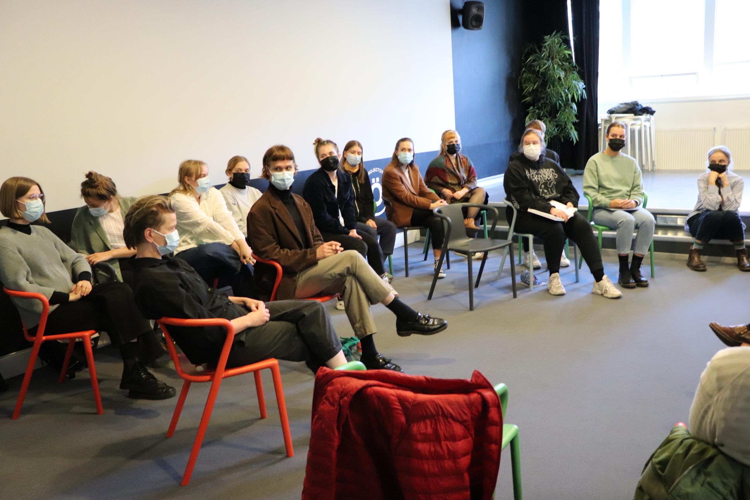 Ryhmä opiskelijoita ja heidän opettajansa istuu tuoleilla ja keskustelee.