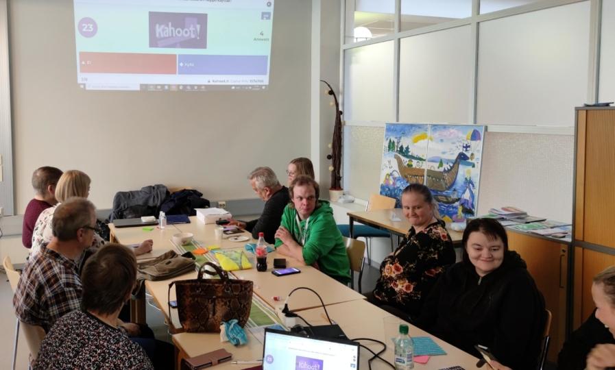 Ihmisiä istuu pöydän ääressä keskustellen. Seinälle on heijastettu tietokoneen näyttö, jossa saavutettavuusvisa.
